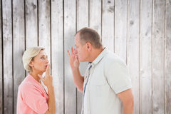 Composite image of older couple holding hands to mouth for silence Stock Photos