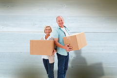 Composite image of older couple smiling at camera holding moving boxes Royalty Free Stock Image