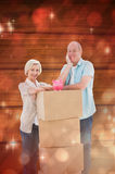 Composite image of older couple smiling at camera with moving boxes and piggy bank Royalty Free Stock Photos