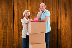 Composite image of older couple smiling at camera with moving boxes and piggy bank Stock Photography