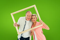 Composite image of older couple smiling at camera through picture frame Royalty Free Stock Images