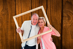 Composite image of older couple smiling at camera through picture frame Royalty Free Stock Photography