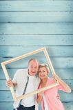 Composite image of older couple smiling at camera through picture frame Royalty Free Stock Photo