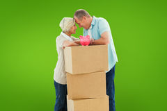 Composite image of older couple smiling at each other with moving boxes and piggy bank. Older couple smiling at each other with moving boxes and piggy bank royalty free stock photography