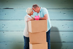 Composite image of older couple smiling at each other with moving boxes and piggy bank. Older couple smiling at each other with moving boxes and piggy bank stock photo