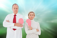 Composite image of older couple standing holding broken pink heart Royalty Free Stock Images