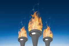 Composite image of the olympic fire. The olympic fire against blue sky Stock Images