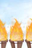 Composite image of the olympic fire. The olympic fire against blue sky with clouds Stock Photography