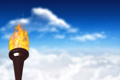 Composite image of the olympic fire. The olympic fire against bright blue sky with clouds Stock Images