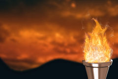 Composite image of the olympic fire. The olympic fire against sky and mountains Stock Photography
