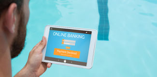 Composite image of online banking text on phone display. Online banking text on phone display against lifeguard using digital tablet at poolside Stock Photo