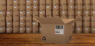 Composite image of open cardboard box by stack of boxes. Open cardboard box by stack of boxes against room with brick wall Royalty Free Stock Images
