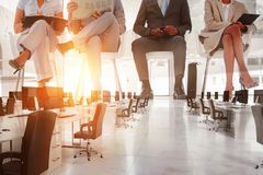 Composite image of open space with black computers. Open space with black computers against group of well dressed business people waiting Royalty Free Stock Photography