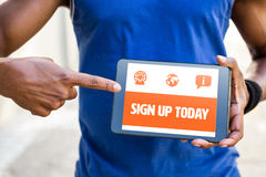 Composite image of orange sign up today. Orange sign up today against man pointing at blank screen of digital tablet Royalty Free Stock Image