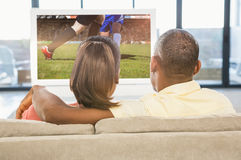 Composite image of over shoulder view of casual couple watching tv Royalty Free Stock Photography