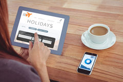 Composite image of over shoulder view of hipster woman using tablet. Over shoulder view of hipster woman using tablet against holidays booking app Royalty Free Stock Photo