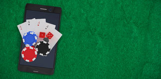 Composite image of overhead view of mobile phone with casino tokens and playing cards Stock Images