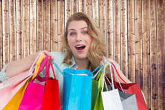 Composite image of overwhelmed young woman with shopping bags Royalty Free Stock Image