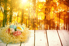 Composite image of patterned easter eggs in paper nest Stock Images