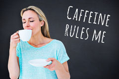 Composite image of peaceful blonde drinking hot beverage with eyes closed. Peaceful blonde drinking hot beverage with eyes closed against black background Royalty Free Stock Image