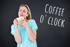 Composite image of peaceful blonde with hot beverage relaxing Stock Image