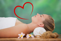 Composite image of peaceful blonde lying on bamboo mat with flowers Royalty Free Stock Photos