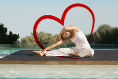 Composite image of peaceful brunette in janu sirsasana yoga pose poolside. Peaceful brunette in janu sirsasana yoga pose poolside against heart Royalty Free Stock Images