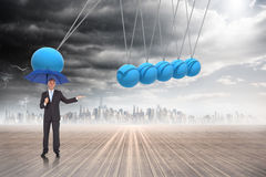 Composite image of peaceful businessman holding blue umbrella Stock Photo