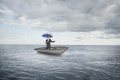 Composite image of peaceful businessman holding blue umbrella in a sailboat Royalty Free Stock Images