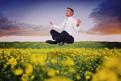 Composite image of peaceful businessman sitting in lotus pose Stock Images