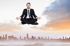 Composite image of peaceful businessman sitting in lotus pose relaxing Royalty Free Stock Image