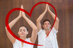 Composite image of peaceful couple in white doing yoga together with hands raised. Peaceful couple in white doing yoga together with hands raised against heart Royalty Free Stock Image
