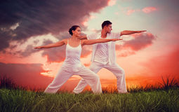 Composite image of peaceful couple in white doing yoga together in warrior position. Peaceful couple in white doing yoga together in warrior position against red Royalty Free Stock Photos