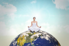 Composite image of peaceful woman in white sitting in lotus pose. Peaceful woman in white sitting in lotus pose against blue sky Stock Photography