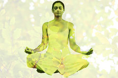 Composite image of peaceful woman in white sitting in lotus pose Royalty Free Stock Photo