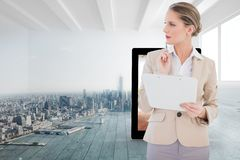 Composite image of pensive blonde businesswoman holding clipboard Royalty Free Stock Image