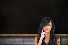 Composite image of pensive elegant brown haired model posing with finger on her cheek Stock Image