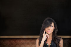 Composite image of pensive elegant brown haired model posing with finger on her cheek Royalty Free Stock Images