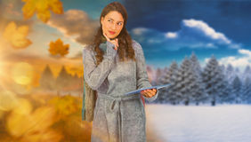 Composite image of pensive model wearing winter clothes holding her tablet Stock Photography
