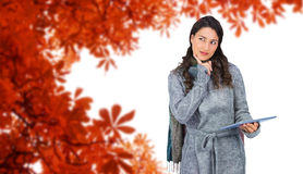 Composite image of pensive model wearing winter clothes holding her tablet Stock Image
