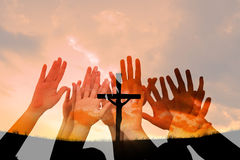 Composite image of people raising hands in the air. People raising hands in the air against cross religion symbol shape over sunset sky Royalty Free Stock Photography