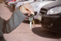 Composite image of person handing keys to someone else. Person handing keys to someone else against cropped image of cars parked in row Stock Photography