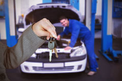 Composite image of person handing keys to someone else. Person handing keys to someone else against mechanic examining under hood of car stock images