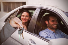 Composite image of person handing keys to someone else. Person handing keys to someone else against young couple smiling while sitting in car Royalty Free Stock Photo