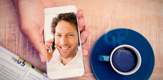Composite image of person using smart phone by coffee and document on table. Person using smart phone by coffee and document on table against closeup portrait of Stock Photography