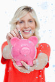Composite image of piggy bank getting dollar notes from a young woman Stock Images