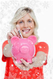 Composite image of piggy bank getting dollar notes from a young woman Stock Image