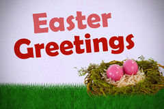 Composite image of pink easter eggs on artificial nest Stock Image