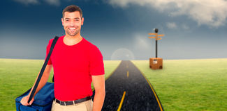 Composite image of pizza delivery man holding bag. Pizza delivery man holding bag against road on grass stock photos