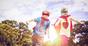 Composite image of playful siblings playing together while disguise as superhero Stock Photos